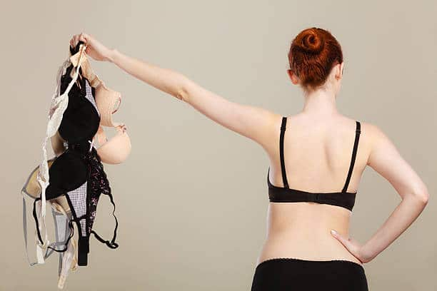 woman holding bras in her left hand why do we wear bad-fitted bras