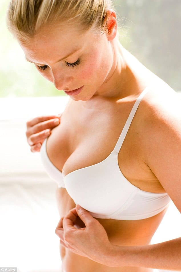 woman in a white bra adjusting band size