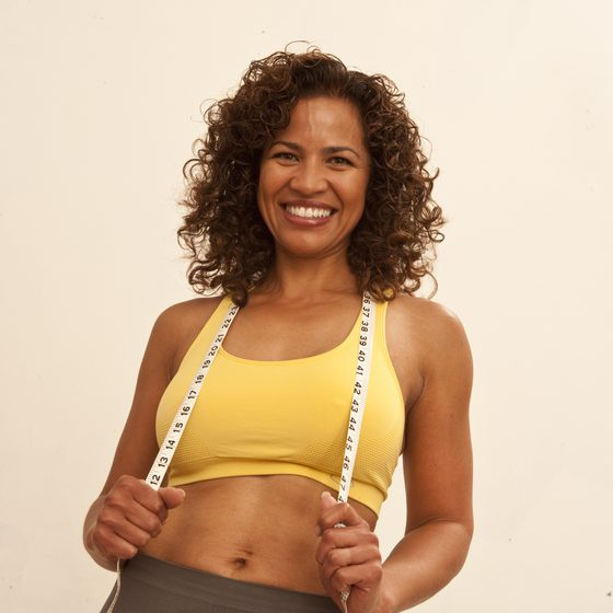 woman holding measuring tape wearing a yellow bra top